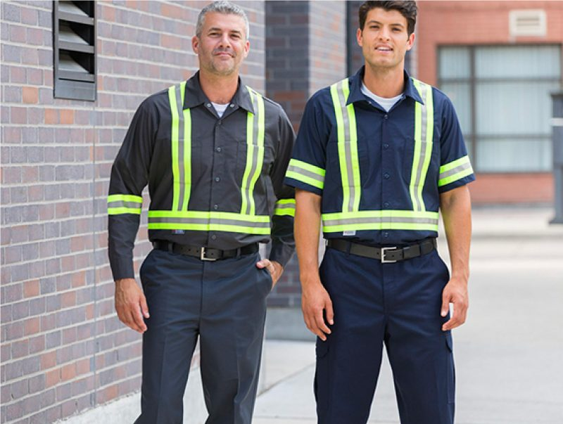 Two industrial workers wearing hi-visibility shirts and pants