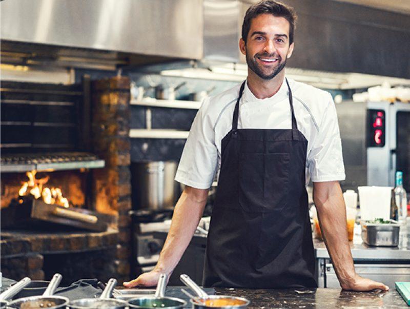 Man smiling in kitchen wearing an apron