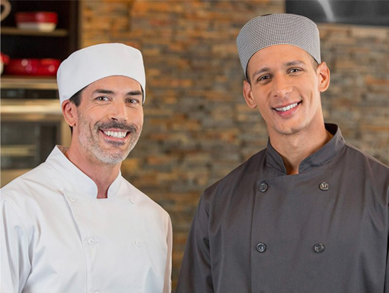 Two chefs smiling wearing pill box caps and chef coats